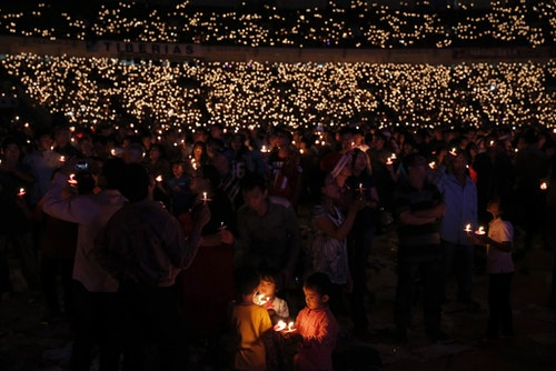 Indonesian Christians hold candles during a Christmas mass prayer session at Gelora Bung Karno stadium in Jakarta