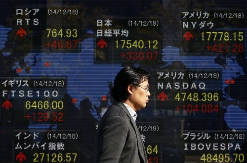A man walks past an electronic board showing the stock market indices of various countries outside a brokerage in Tokyo