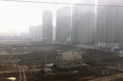 """A """"nail house"""", the last building in the area, is seen surrounded by a ditch at a construction site for a new residential compound in Xiangyang, Hubei province"""