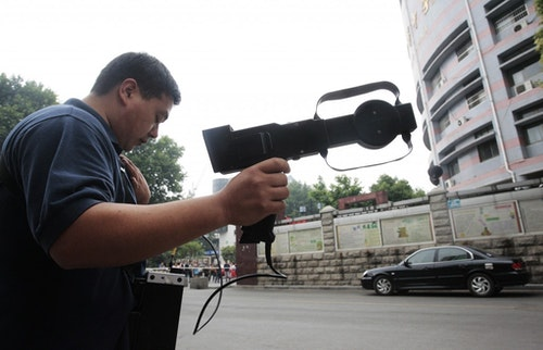 Police scanning for suspicious radio signals outside an exam site. Photo Credit: Reuters