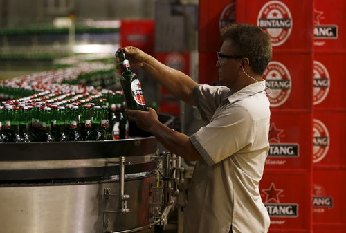 A worker of PT Multi Bintang Indonesia Tbk. holds a bottle of Bintang beer to check the quality at a beer factory in Jakarta