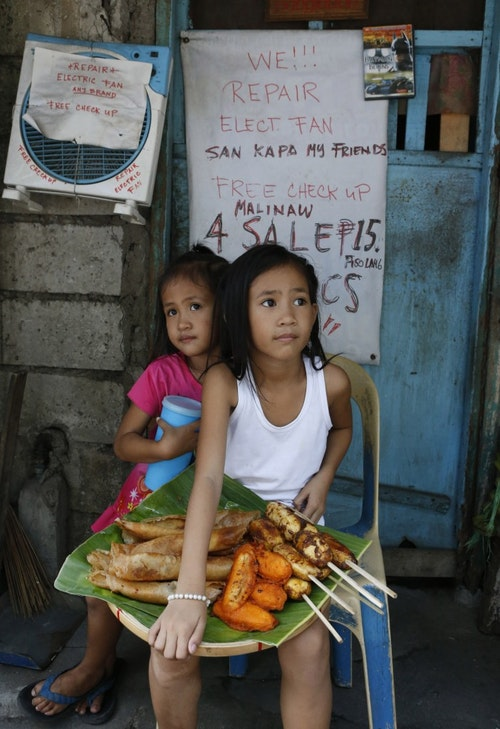 MaryJasmine and MaryAngel sell sweet banana snacks in a squatter colony in Quezon city, Manila