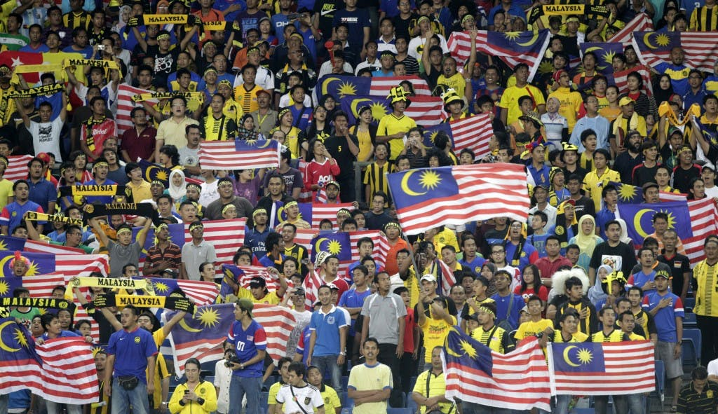 Malaysia fans wave Malaysian national flags in the stands before their semi-final first leg match of the ASEAN Football Federation (AFF) 2010 soccer tournament against Vietnam in Kuala Lumpur