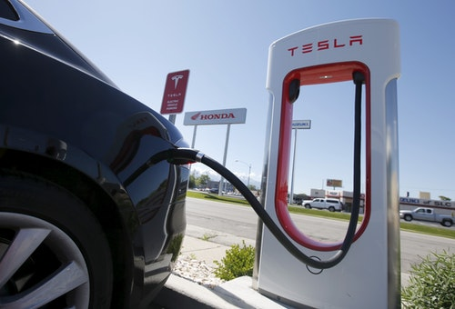 A man charges his Tesla Model S at a charging stations in an empty lot at a new Tesla dealership across from a traditional car dealer in Salt Lake City