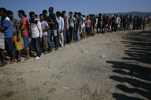"""Migrants line up to receive sandwiches offered by volunteers of the organisation """"Solidarity Kos"""" outside Captain Elias, a derelict hotel where migrants find shelter on the Greek island of Kos"""