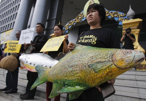 Villagers hold a model of a fish, fish-shaped signs and placards while they pose for photographers at Thailand's Administrative Court in Bangkok June 24, 2014. A Thai court accepted a lawsuit against state-owned Electricity Generating Authority of Thailand (EGAT) and four other state bodies on Tuesday for agreeing to buy electricity from a $3.5 billion hydropower dam being built in neighbouring Laos. The Xayaburi dam, which will be the first on the main stream of the Mekong River in Southeast Asia, is at the heart of landlocked Laos's ambitions to supply power to the region, with Thailand set to buy around 95 percent of the electricity generated. Activists say the project threatens the livelihood of tens of millions who depend on the river's resources. REUTERS/Chaiwat Subprasom (THAILAND - Tags: ENERGY ENVIRONMENT CIVIL UNREST CRIME LAW POLITICS BUSINESS) - RTR3VEYD