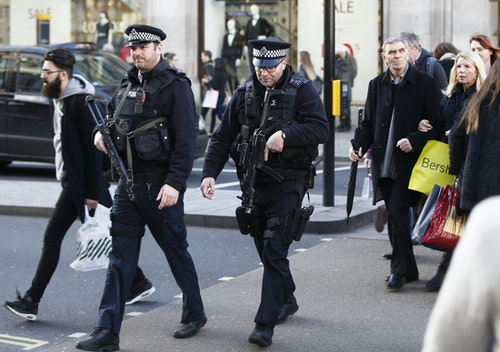 File photograph of armed police walking amongst shoppers along Oxford Street in London