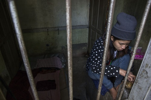 MYITKYINA, BURMA - JANUARY 26: A detainee sits near the window of her small cell at Pat Jasan headquarters on January 26, 2016 in Myitkyina, Burma. Pat Jasan is a Christian anti-drug group in Kachin State claiming over 100,000 members. Dissatisfied with the government's response towards widespread heroin use and poppy growing, the religious organization has taken matters into their own hands, organizing patrols, raiding houses, detaining drug dealers and users, and clearing poppy fields. Their brand of vigilante justice has been labeled extreme with some chapters accused of publicly beating those involved in the drug trade. (Photo by Taylor Weidman/Getty Images)