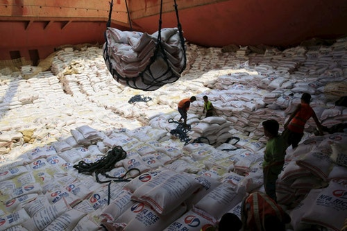 Workers watches sacks of imported Vietnam rice as it is lifted by a crane from a ship docked at a port area in Manila June 8, 2015. The Philippines agreed to buy 150,000 tonnes of rice from Vietnam in a tender on June 5, 2015 and could import additional volumes to avert a potential spike in prices of the staple if adverse weather threatens the local crop. The Philippines' state grains procurement agency, the National Food Authority (NFA), already has government approval to buy another 250,000 tonnes if drought brought on by an El Nino weather phenomenon hurts its harvest and it has the option to import 100,000 tonnes not allocated in Friday's tender. REUTERS/Romeo Ranoco - RTX1FKRJ