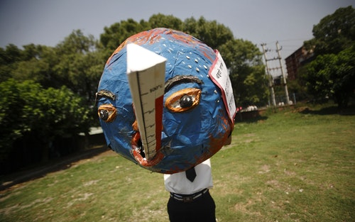 A boy holds a globe, that depicts the effects of global warming, while he returns from a rally organized to mark World Environment Day in Kathmandu