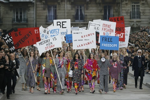 German designer Karl Lagerfeld appears with models who stage a demonstration at the end of his Spring/Summer 2015 women's ready-to-wear collection for French fashion house Chanel in Paris