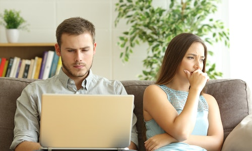 Husband using a laptop on line ignoring to his sad wife sitting on a sofa at home