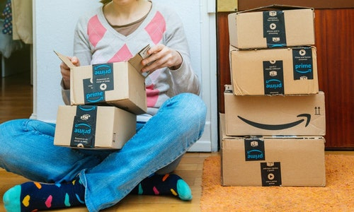 PARIS, FRANCE - JAN 13, 2018: Stack of Amazon Prime packages delivered to a home door woman unboxing one of the small boxes. Amazon is the largest internet based retailer in the United States - 圖片