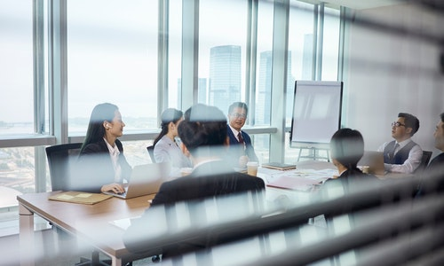 through-the-glass shot of a team of asian business people meeting in company conference room